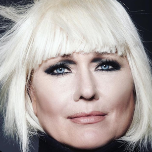 Emme's wearing a blunt bangs platinum blond wig with dark smoky eye makeup, photo is a close up shot of just Emme's face