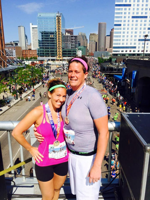 Fawn and her husband smiling after both finishing a half marathon and becoming engaged right then and there. Both are wearing athletic clothes and their finisher medals