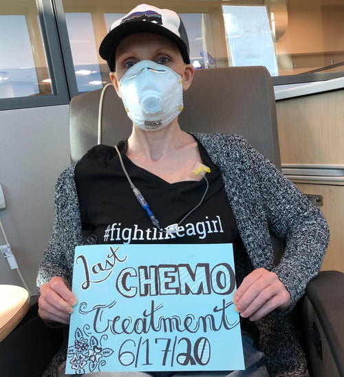 Tracee on her last day of chemo therapy holding a sign and wearing a mask