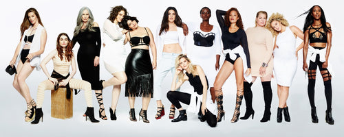 Group Modeling Shot, everyone is dressed in some manner of black, white and cream colors but each model is diverse in color and age, Emme is in knee high black boots and a turtleneck beige dress