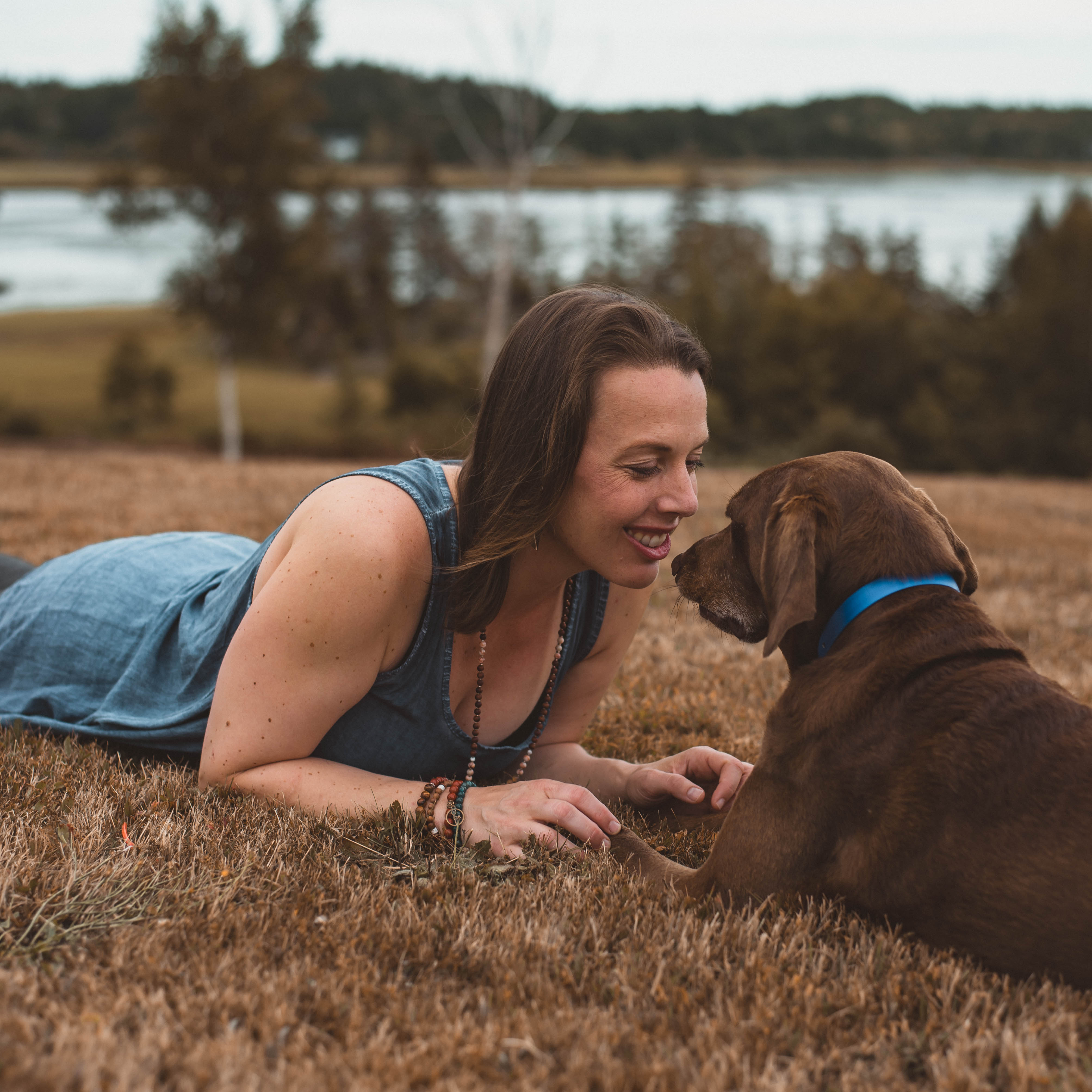 Kate looking lovingly at her chocolate brown lab, laying in the grass alongside water