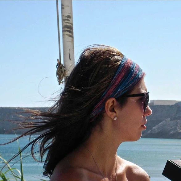 Elise is looking pensive as she stands next to the ocean, wind blowing through her brown hair