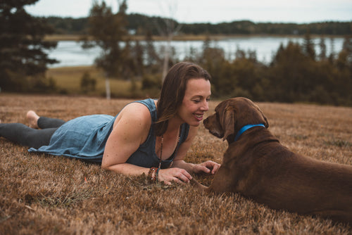 Kate looking lovingly at her dog as she lays in the grass next to a large body of water.