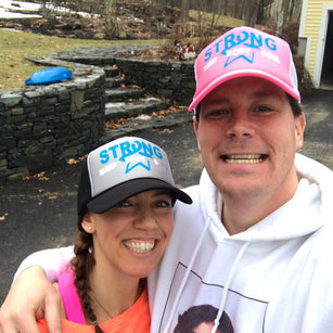 Fawn and her husband both wearing their colon cancer survivor hats during colon cancer awareness month, its a selfie with big smiles