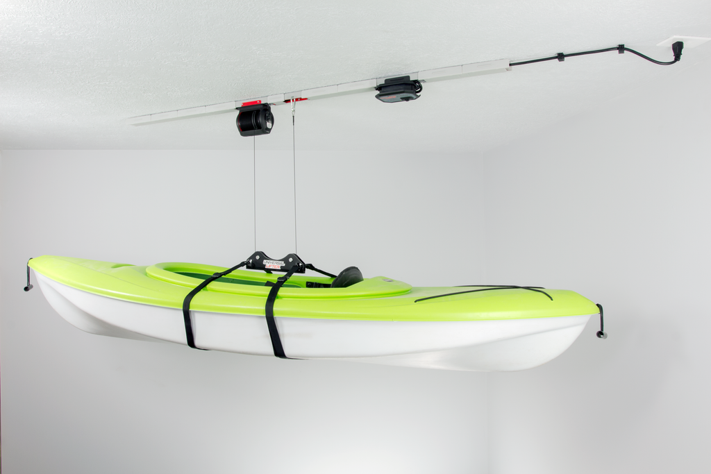 One green kayaks that are hanging from the ceiling of a storage unit.
