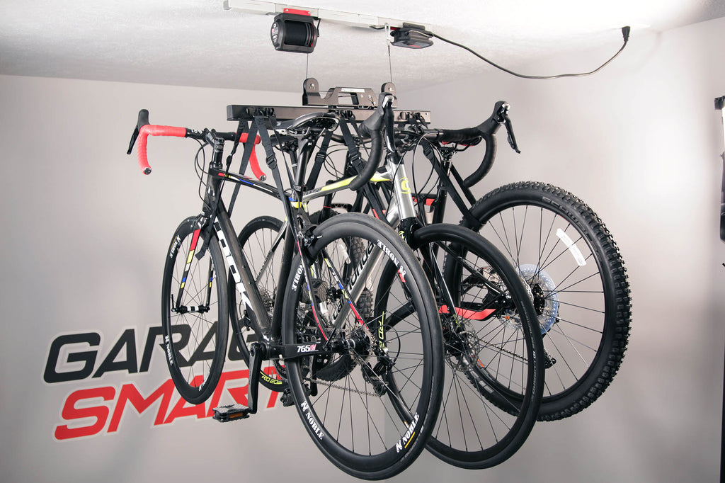 A Garage Smart bike rack that is pulling up three bikes for ideal garage storage.