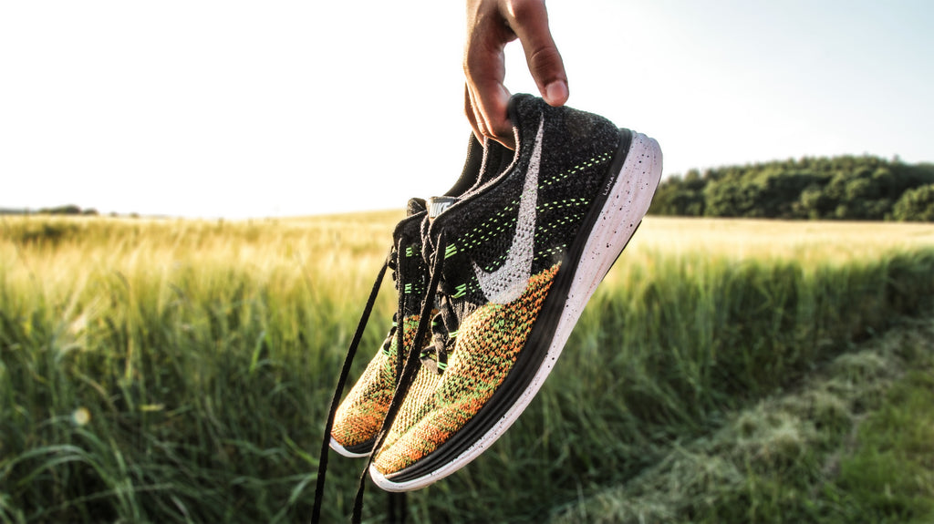 A pair of Nike running shoes that are being held in front of a scenic green field.