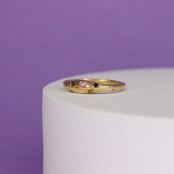 product shot of 9k yellow gold ring with sapphire gemstones sitting on white plinth against a purple background
