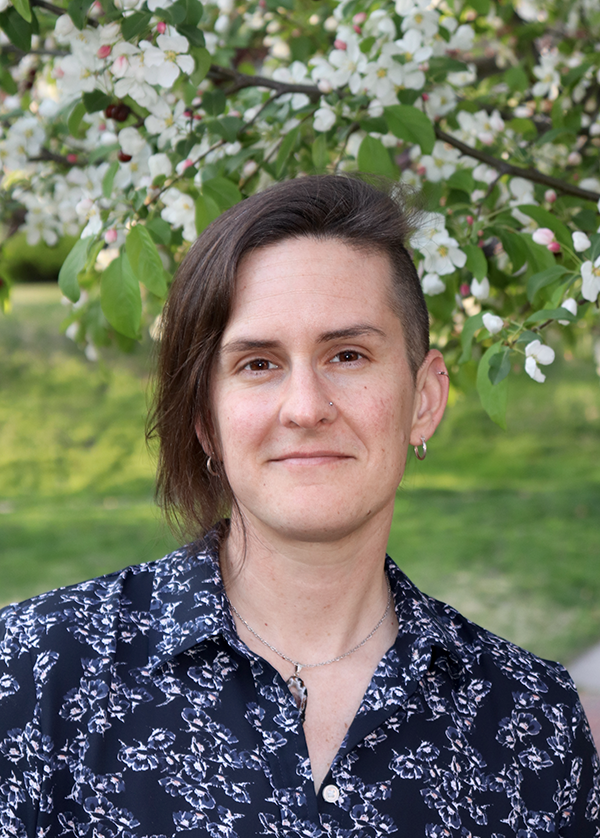 Rev. M Barclay - a white nonbinary trans and queer person with a decidedly asymmetrical haircut is wearing a dark blue floral shirt and stands under a tree limb with white flowers.