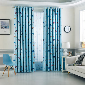 Blue Kids Blackout Curtains with Cartoon Car Prints Shown Bi partisan and half open on a window in dual layer setting in a kids bedroom.