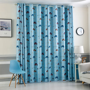 Blue Kids Blackout Curtains with Cartoon Car Prints Shown closed on a window in a room setting.