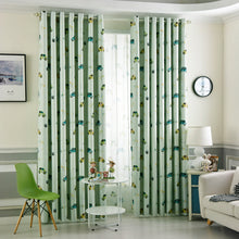 Green Kids Blackout Curtains with Cartoon Car Prints Shown Bi partisan and half open on a window in dual layer setting in a kids bedroom.
