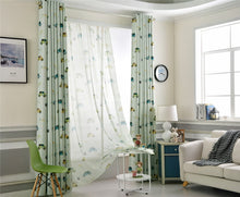 Blue Kids Blackout Curtains with Cartoon Car Prints Shown Bi partisan and 80% open on a window in dual layer setting in a kids bedroom.