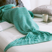 a woman reading a book on the bed and wearing a turquoise comfortable knit mermaid tail blanket