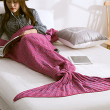 a woman reading a book on the bed and wearing a burgandy color comfortable mermaid tail blanket