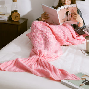 a woman reading a book on the bed and wearing a hot pink color comfortable mermaid tail blanket