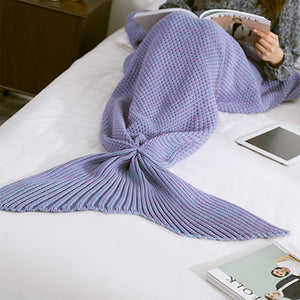 a woman reading a book on the bed and wearing a purple color comfortable mermaid tail blanket