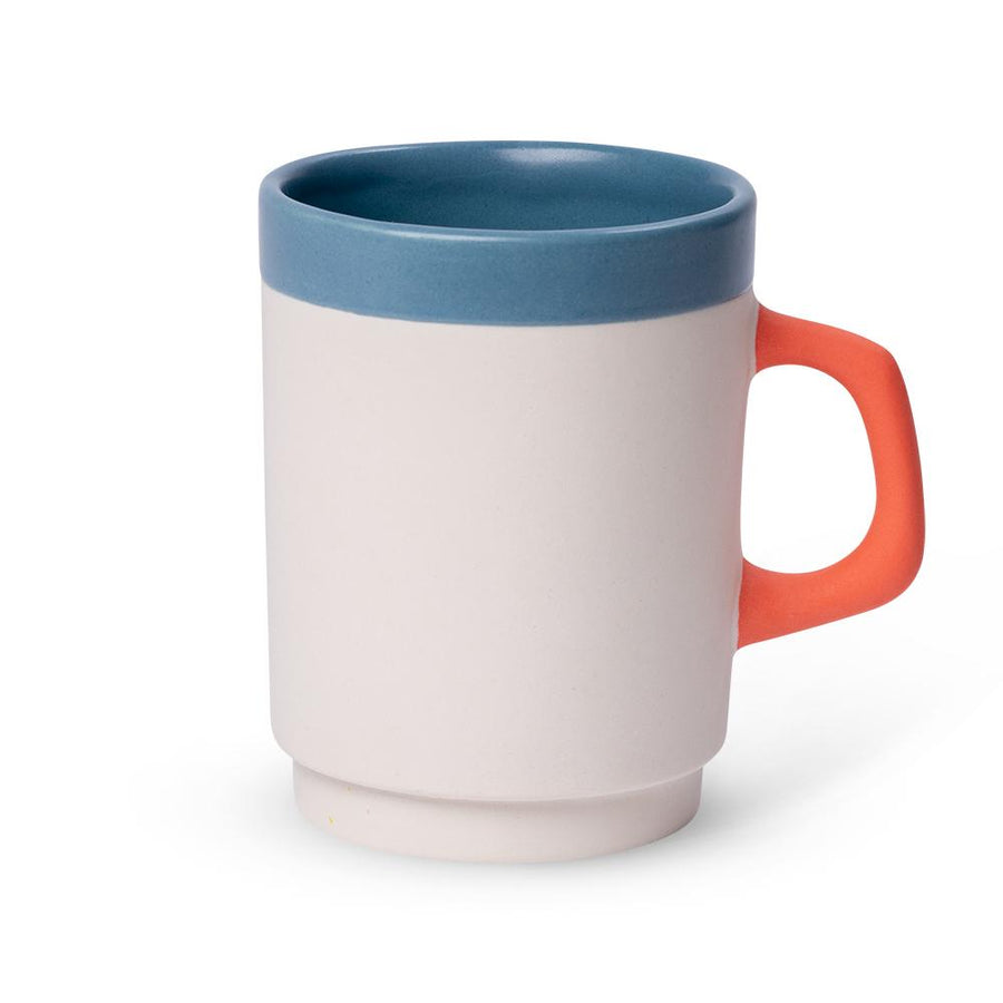 a white diner mug with a blue rim and orange handle