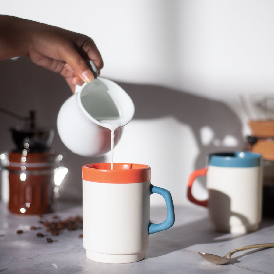 cream being poured into a white diner mug with an orange rim and blue handle