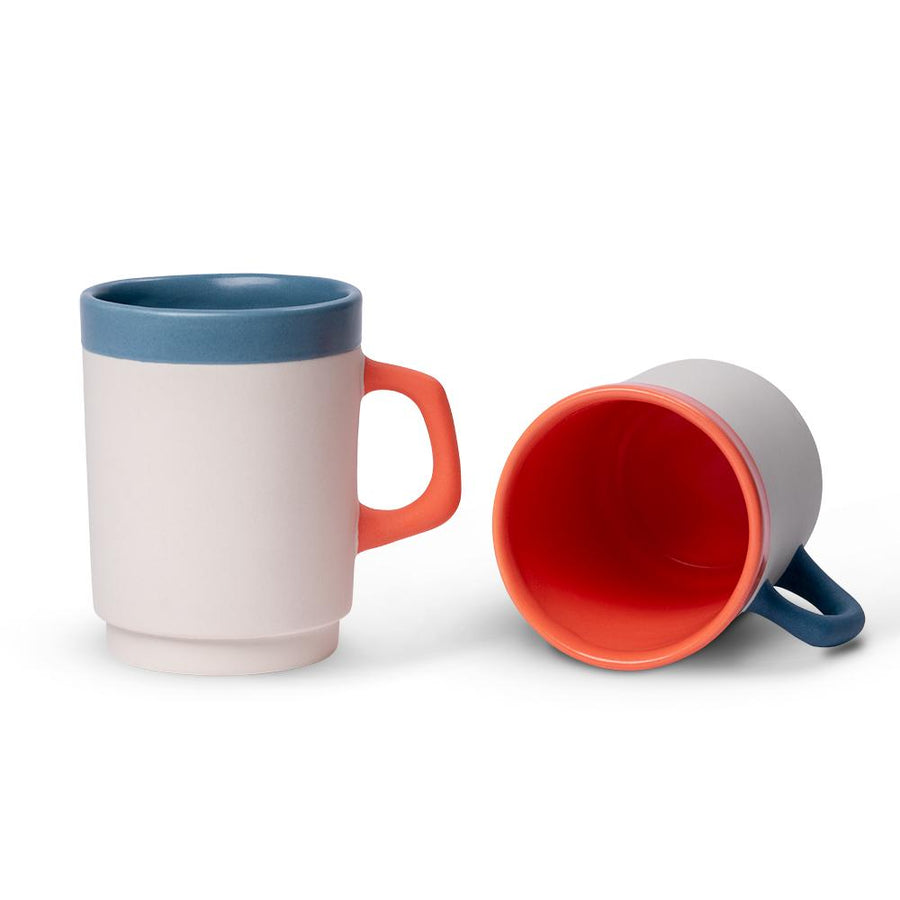 a white diner mug with a blue rim standing beside a tipped over white diner mug with an orange rim and interior rim