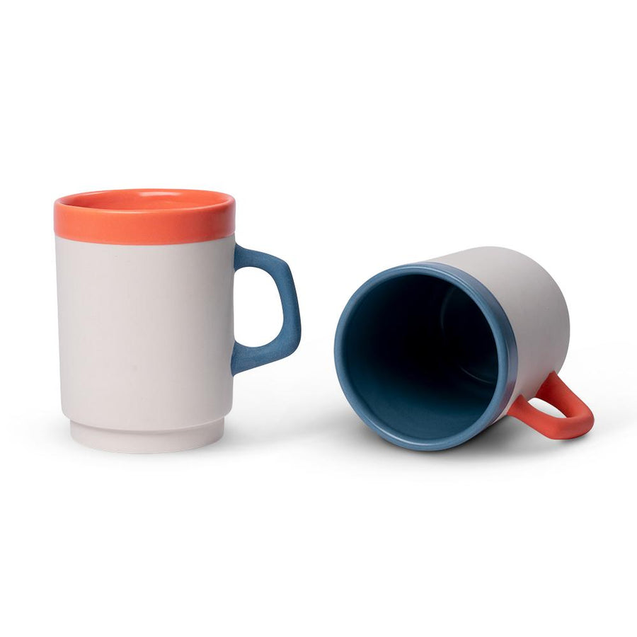 a white diner mug with an orange rim standing beside a tipped over white diner mug with a blue rim