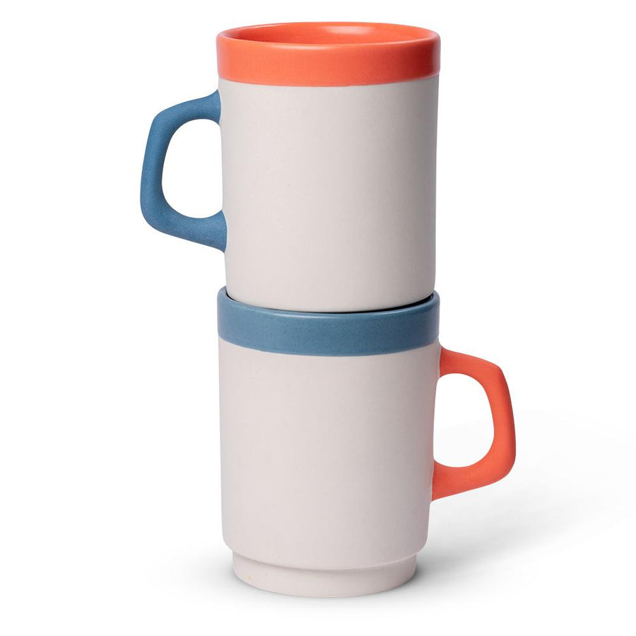 a white diner mug with an orange rim and blue handle stacked on top of a white diner mug with a blue rim and an orange handle