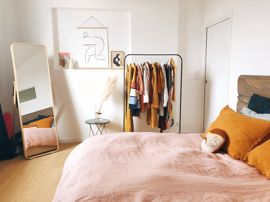 bedroom with mirror, clothes rack and orange pillows