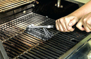 bbq grill being cleaned with a wire brush