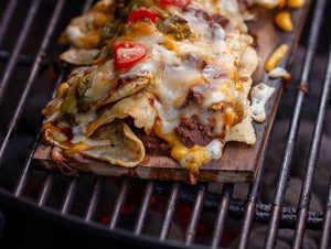 Nachos cooking on a wood grilling plank