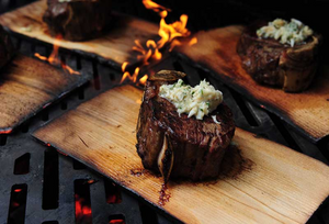 Filet mignon steak cooking on wood grilling plank