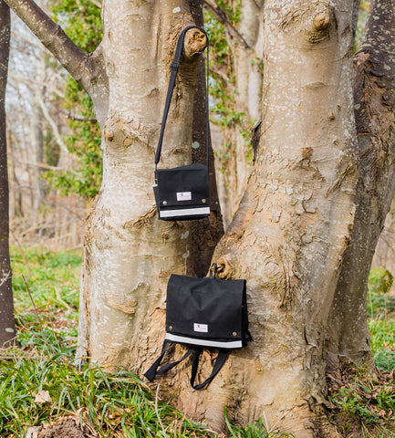 Dogrobes' Dog Walking Bags hanging on a tree trunk