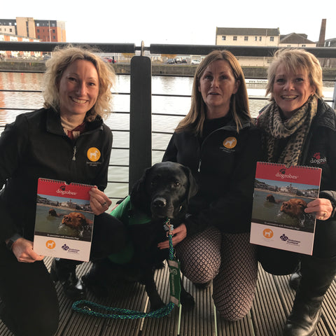 Fiona and Nadia from The Dementia Dog project with Margaret from Dogrobes and Alex (black labrador) showing the new charity calendar
