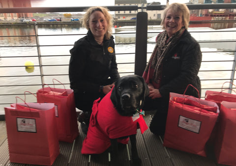 Margaret Reynolds, owner of Dogrobes delivering drying coats to Fiona Corner of The Dementia Dog Project. Black labrador, Webb at front wearing a red Dogrobe.