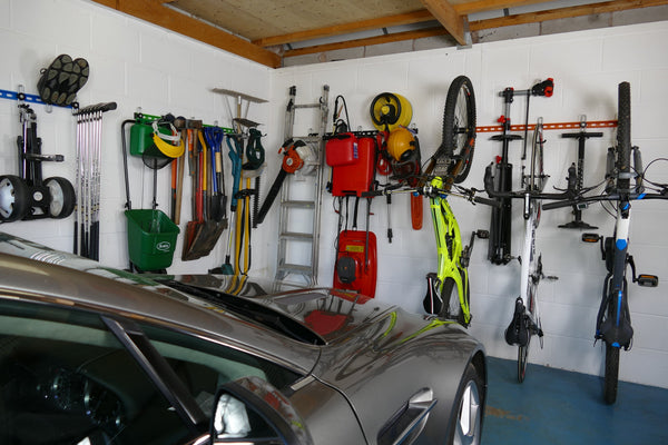 Inside of a garage with wall mounted storage racks showing how bikes, sports equipment and garden tools can be stored on wall mounted racks and leave space for a car
