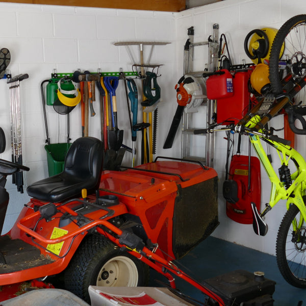 Inside of a garage with wall mounted storage racks showing how bikes, sports equipment and garden tools can be stored on wall mounted racks