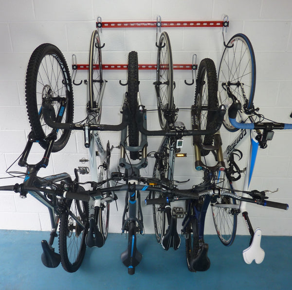 Two GearHooks bike storage racks mounted one above the other and shown holding  2 mountain bikes, 1 electric bike and 3 road bikes