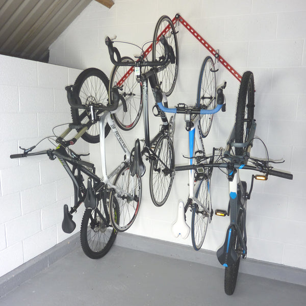 Flying V garage bike storage rack showing 2 GearRails and 5 bike storage hooks mounted in an inverted v shape with 2 mountain bikes and 3 road bikes