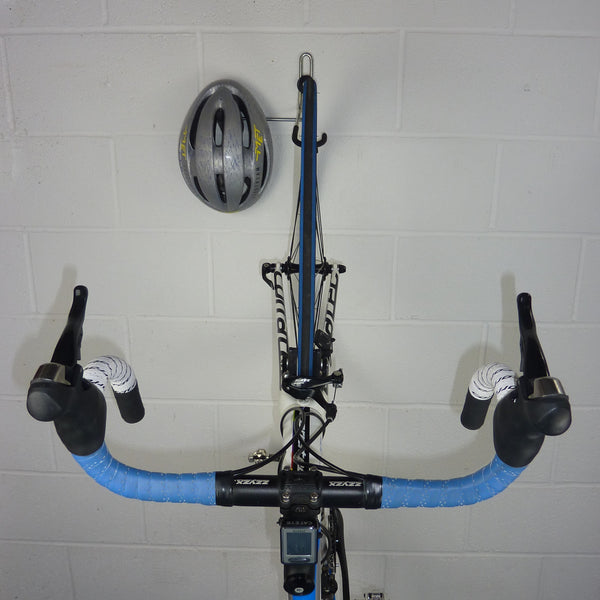 wall mounted bike hook for 1 bike and biking gear shown with a road bike and helmet