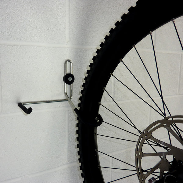 wall mounted bike hook for 1 bike and biking gear shown with a mountain bike