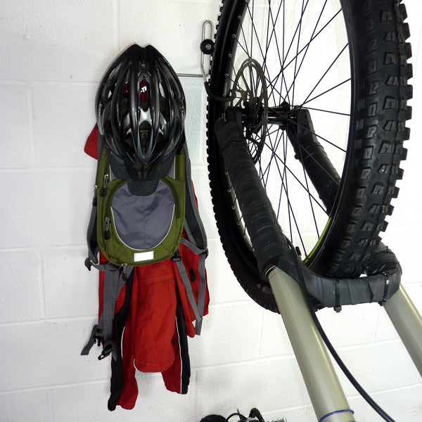 wall mounted bike hook for 1 bike and biking gear shown with a mountain bike, backpack, coat and helmet