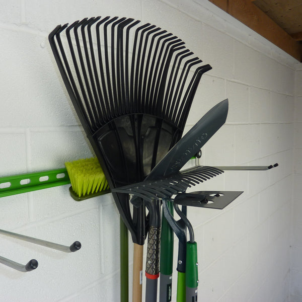 Garden tool rack with a hook holding 6 tools including a broom, leaf rake, trenching spade, rake, large and small hoes