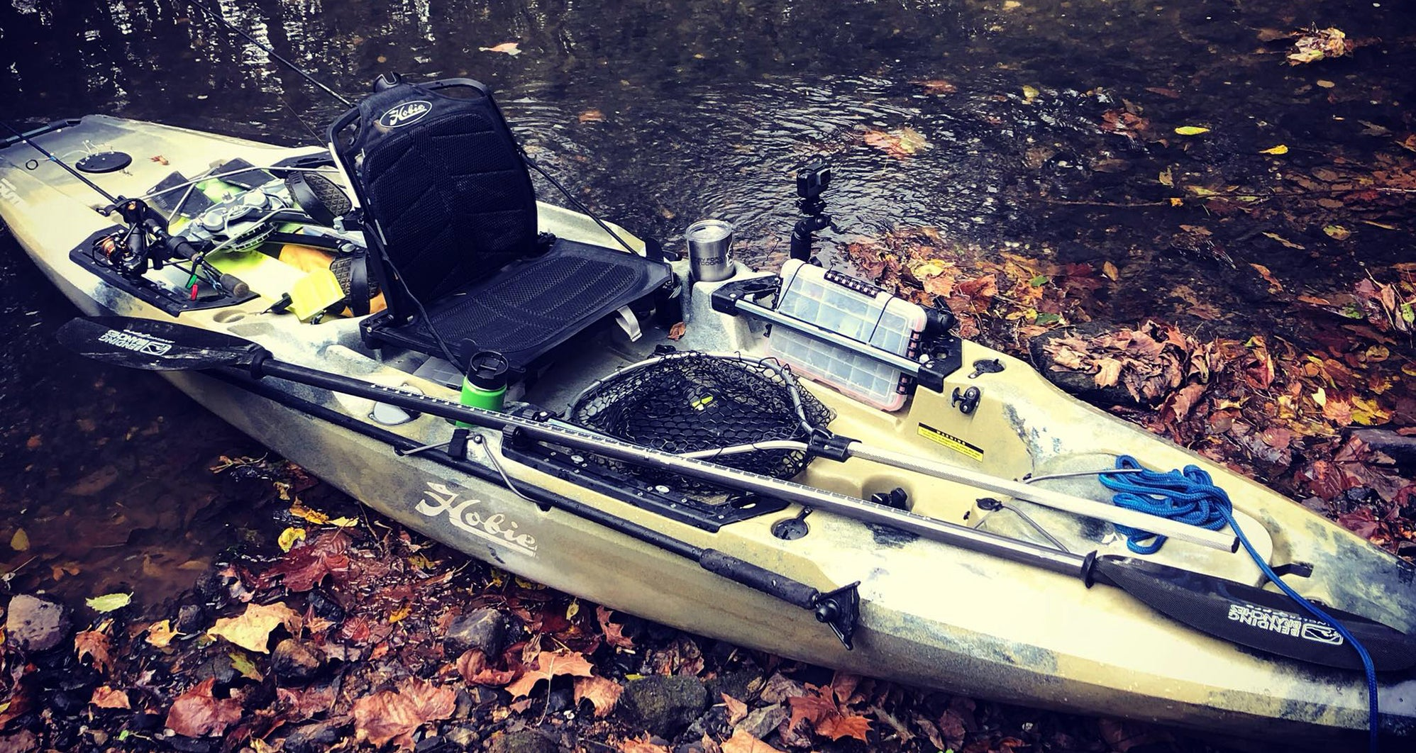 Hobie Outback Kayak on the bank of a shallow creek with fall foilage floating in the water