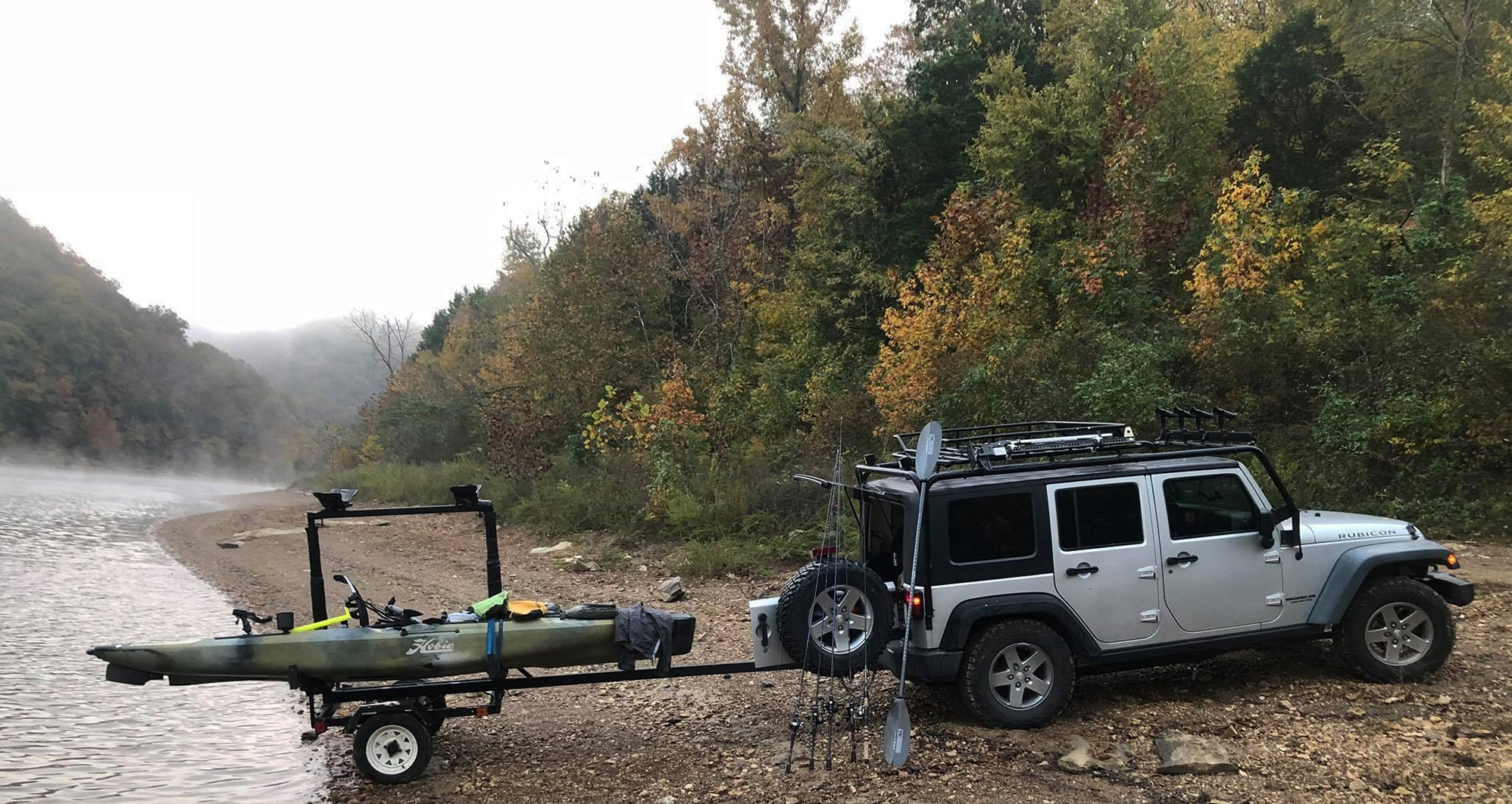 Jeep Wrangler 4 door with a trailer backed up to the lake.  Kayak is on the trailer being ready to launch.