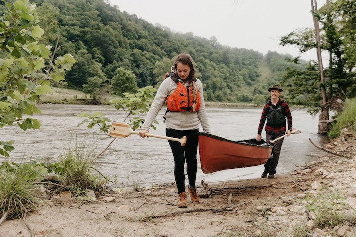 canoiests with paddles and canoe