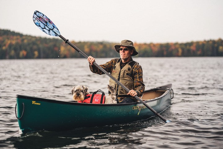 canoeist and dog in solo canoe