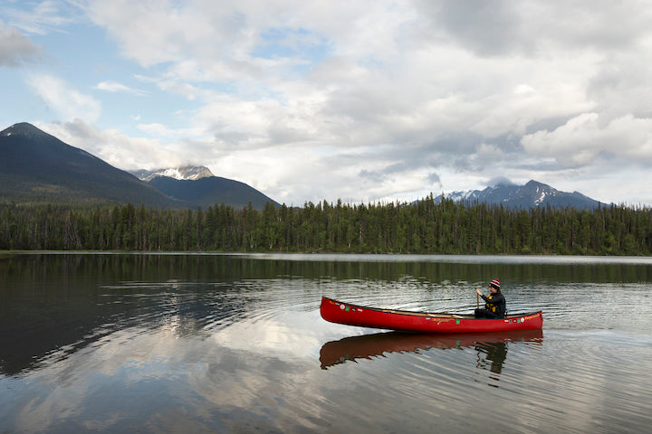 canoeist paddling solo in a tandem canoe
