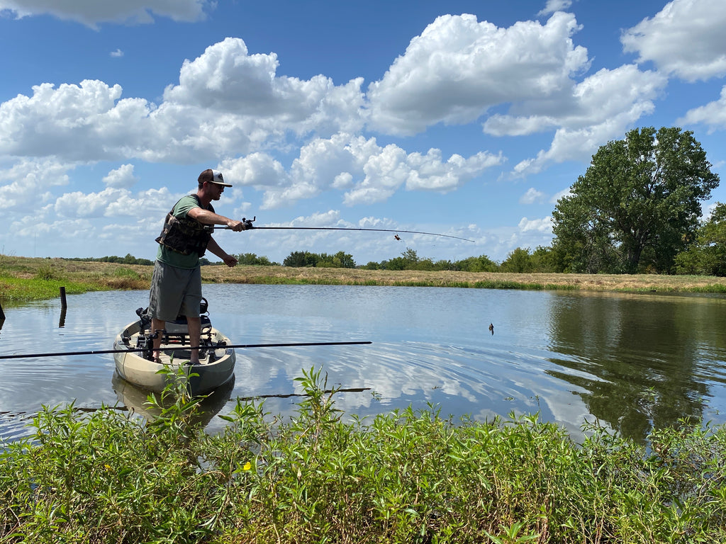 A man fishing from his kayak standing up
