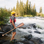 Person holding java paddle standing on rock looking at whitewater