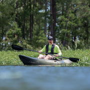 Kayak angler sitting in a kayak near the forest
