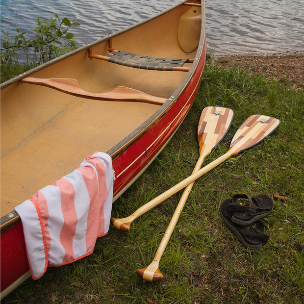 2 canoe paddles laying on the ground next to canoe